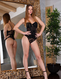 Vanesa admire her reflection in the giant mirror as she poses in her black lace lingerie and strappy stiletto heels